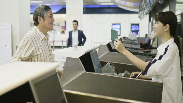 asian senior man giving passport to airline check-in attendant - airline check in attendant stock videos and b-roll footage