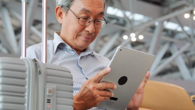 アジアの先輩男性は、彼の研究室の画面を見て、微笑んでいます。彼は空港に座っている。旅行、旅、グローバル、ライフスタイル、休日、技術の概念。空港内 - passenger点の映像素材/bロール