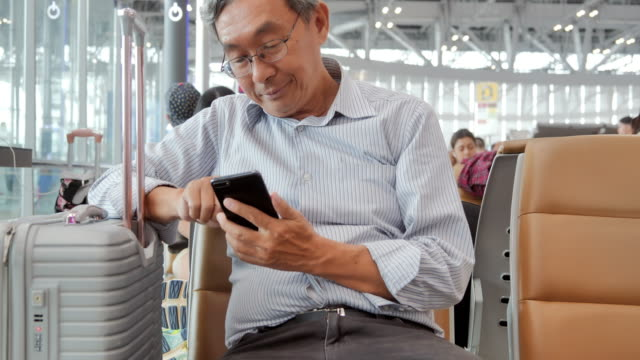 asian senior man is looking at screen of his mobile phone.he is sitting at airport.travel,journey,global,lifestyle,holidays,technology concept.in the airport - ethnicity stock videos & royalty-free footage