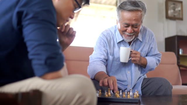 asian senior man playing chess with son at home - chess stock videos & royalty-free footage