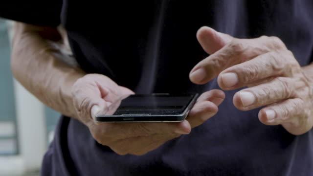 stockvideo's en b-roll-footage met aziatische senior man met moble telefoon - pensioen thema