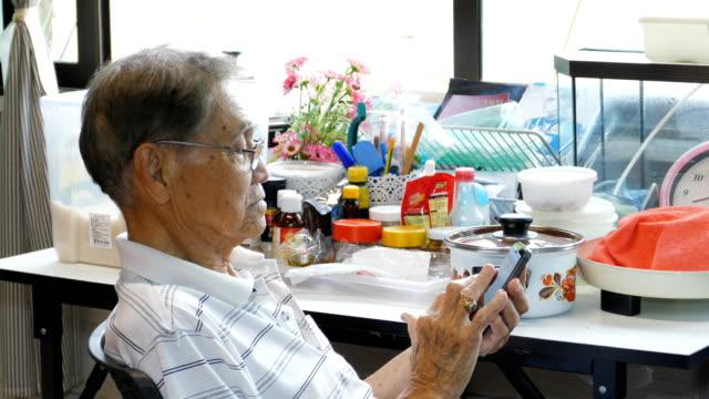 スマートフォンを使ったアジアのシニア男性。 - senior men点の映像素材/bロール