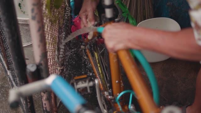 vídeos de stock e filmes b-roll de asian senior man wash and clean the vintage moutain bike. - ciclo