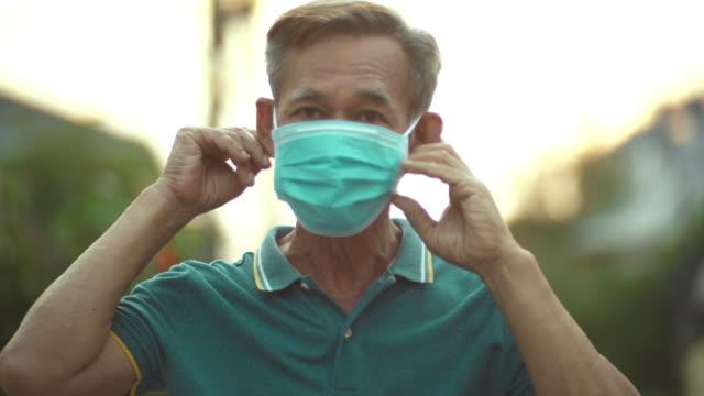 vidéos et rushes de homme aîné asiatique avec le masque hygiénique - appliquer