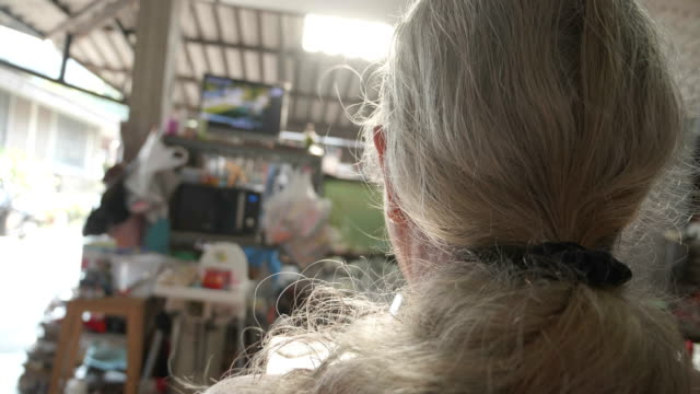Asian Senior man with long white hair watch Movie on TV.