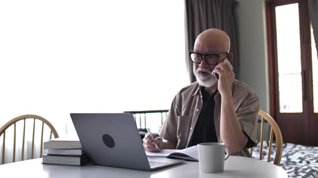 asian senior man working at home - working seniors stock videos & royalty-free footage