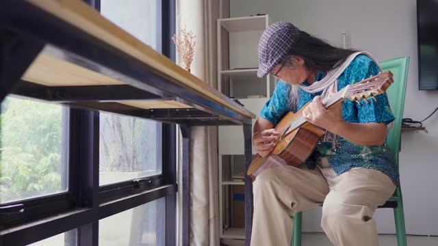 asiatische senioren spielen gerne gitarre im wohnzimmer zu hause - gitarre stock-videos und b-roll-filmmaterial