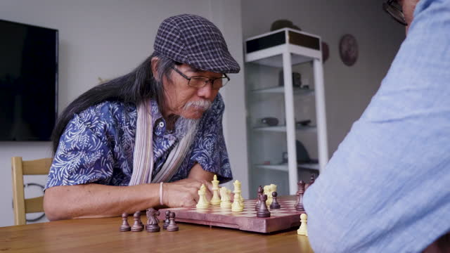 asian senior men friends playing chess in living room at home, active senior people concept - rivalry stock videos & royalty-free footage