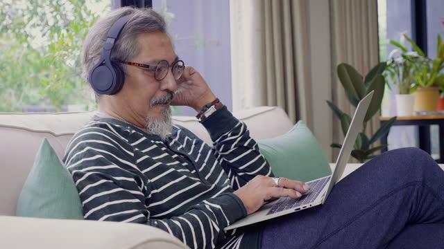 vidéos et rushes de hommes aînés asiatiques écoutant la musique avec le casque et utilisant l'ordinateur portatif tout en fixant sur le sofa dans le salon à la maison - asian and indian ethnicities