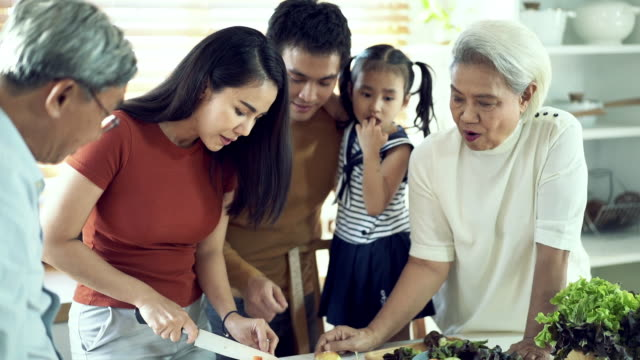 asian senior mother teaching family how to cooking in kitchen - stereotypical homemaker stock videos & royalty-free footage