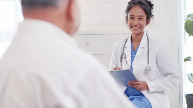 asian senior old man listening to young black female nurse doctor in consultation to his older male patient at home.medical,caretaking,care,retirement,volunteer,education,nursing home,caregivers at home,medicine and health care - visit stock videos & royalty-free footage