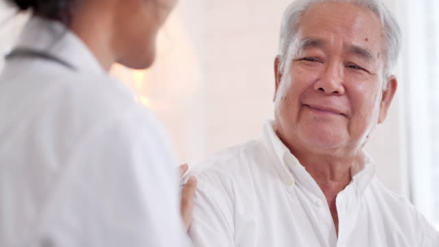 asian senior old man listening to young black female nurse doctor in consultation to his older male patient at home.medical,caretaking,care,retirement,volunteer,charity,education,nursing home,caregivers at home,medicine and health care - sad old asian man stock videos & royalty-free footage