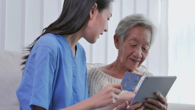 asiatische senior alte frau zu hören asiatische junge krankenschwester arzt erklärt medizin zu ihrer älteren patientin zu hause. hausgesundheitskonzept. - moving image stock-videos und b-roll-filmmaterial