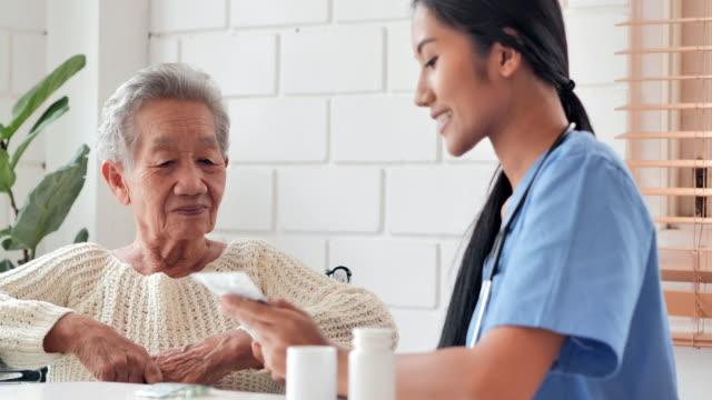 自宅で彼女の年上の女性患者に薬を説明する若い黒人女性看護師の医師に耳を傾けるアジアの先輩の老婦人。医療、ケア、介護、退職、ボランティア、慈善、教育、老人ホーム、家庭での介� - 介護点の映像素材/bロール