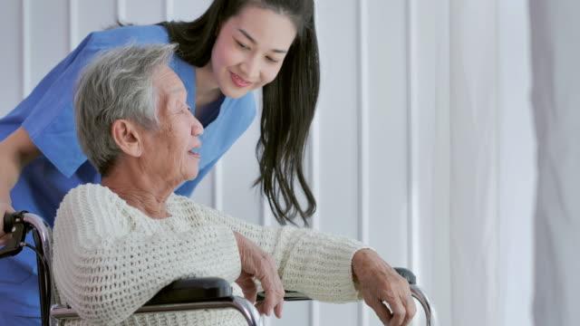 車椅子に座って、自宅や病院の窓に近いアジアの若い女性看護師の医者と話しているアジアの先輩女性。高齢の祖母は、介護者が支援を与えることを聞く,高齢者のヘルスケア,ホームヘルス� - 介護点の映像素材/bロール
