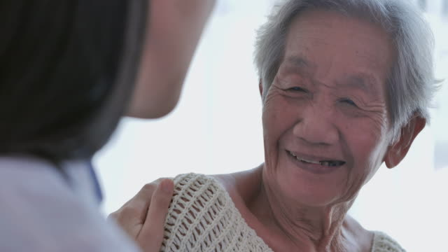 asian senior old women listening to asian young female nurse doctor in consultation and holding hand to her older female patient at home.at home caregiver - emotional support stock videos & royalty-free footage