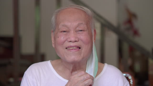 asian senior removing facial mask and smile - obscured face stock videos & royalty-free footage