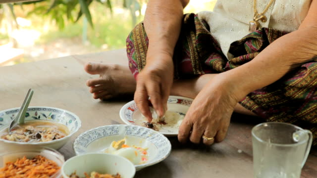 Asian senior woman alone eating