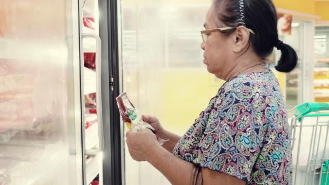 Asiatisk senior kvinna att köpa fryst mat i snabbköpet.