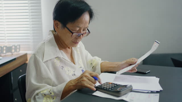 asian senior woman calculates monthly expenses check receipts to pay . - retirement stock videos & royalty-free footage