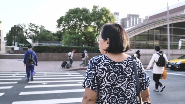 asian senior woman crossing the street. taipei, taiwan - large group of people stock videos & royalty-free footage