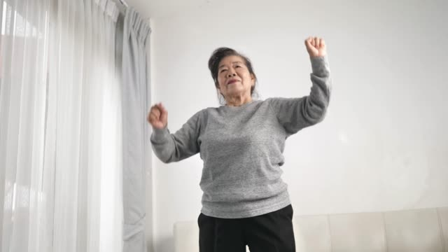 asian senior woman doing exercise and dancing at home, stay home lifestyle concept. slow motion. - dance studio stock videos & royalty-free footage