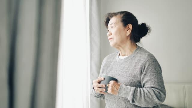 asian senior woman drinking hot tea near window outdoor, quarantine concept. - tea hot drink stock videos & royalty-free footage