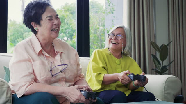 asian senior woman friends enjoy playing video games together in living room at home - video stock videos & royalty-free footage