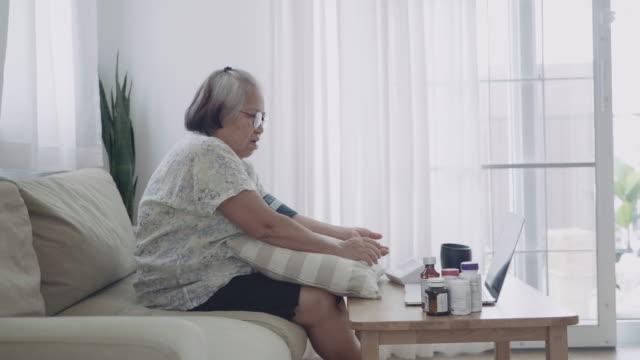 asian senior woman measuring blood pressure at home. - doctor multitasking stock videos & royalty-free footage
