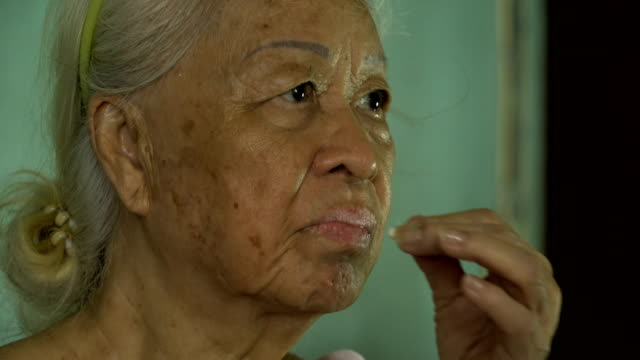 Asian senior woman minerals pills in hand and taking glass of water.