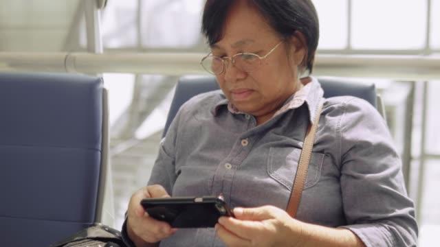 vídeos de stock e filmes b-roll de asian senior woman passenger using smartphone in the terminal airport waiting for her flight - banco assento
