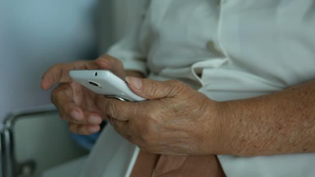 携帯電話を用いたアジアの年配の女性患者 - 年配の女性点の映像素材/bロール