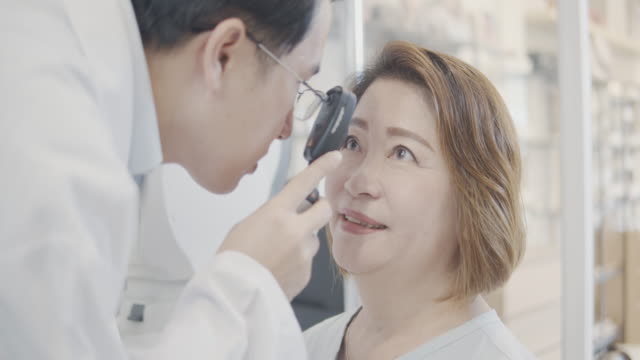 asian senior woman patients checking eye in optometrist store by doctor.using auto refractor,phoropter,trial frame,brock string,va chart,monitor chart and torch for checking eye.eye symptomatology in a senior man.medical education,health care. - lens optical instrument stock videos & royalty-free footage