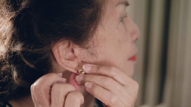 asian senior woman putting her earrings and make-up - orecchini video stock e b–roll