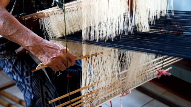 asian senior woman silk weaving at home , old culture ,thai traditional, making silk clothing. concept : hand craft, classic, culture, clothing. - filo articolo di merceria video stock e b–roll