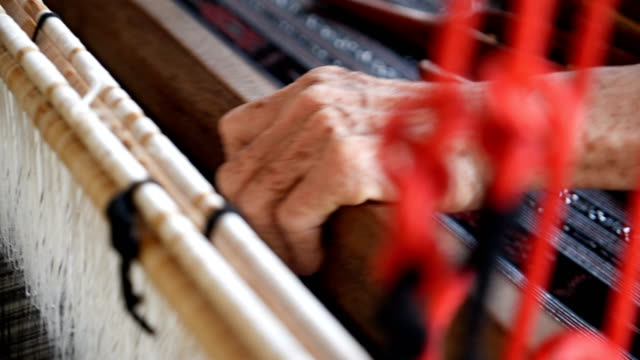 Asian Senior woman silk weaving at home , old culture ,Thai traditional, making silk clothing. Concept : hand craft, Classic, Culture, clothing.