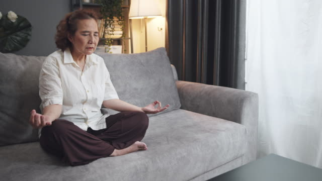 pov asian senior woman sitting and meditation in the lotus pose at home. mature woman sitting cross legged. retried and calm old female relieve stress by practicing yoga. focus training  or manage emotions - cross legged stock videos & royalty-free footage