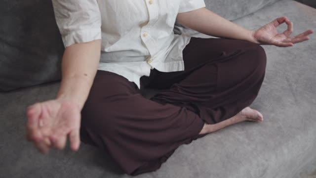 asian senior woman sitting and meditation in the lotus pose at home. mature woman sitting cross legged. retried and calm old female relieve stress by practicing yoga. focus training  or manage emotions - cross legged stock videos & royalty-free footage