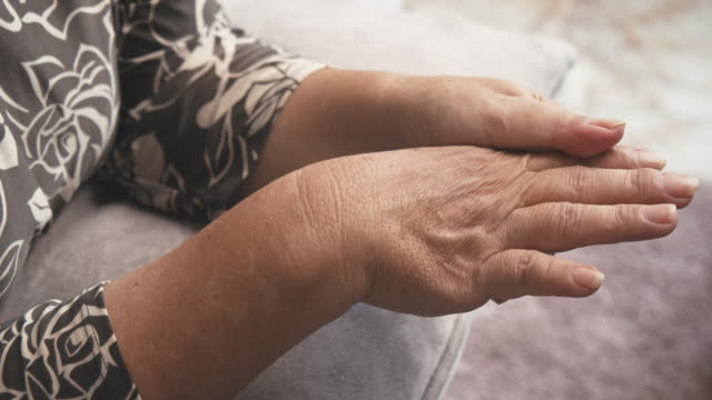 Asian senior woman sitting on a couch having a hand pain.massage on her hand