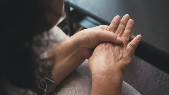 asian senior woman sitting on a couch having a hand pain.massage on her hand - pain stock videos & royalty-free footage