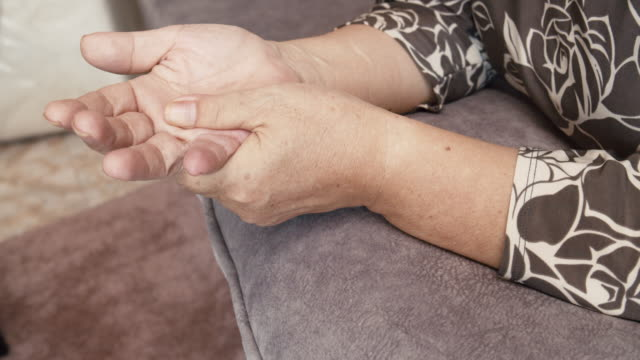 asian senior woman sitting on a couch having a hand pain.massage on her hand - human hand stock videos & royalty-free footage