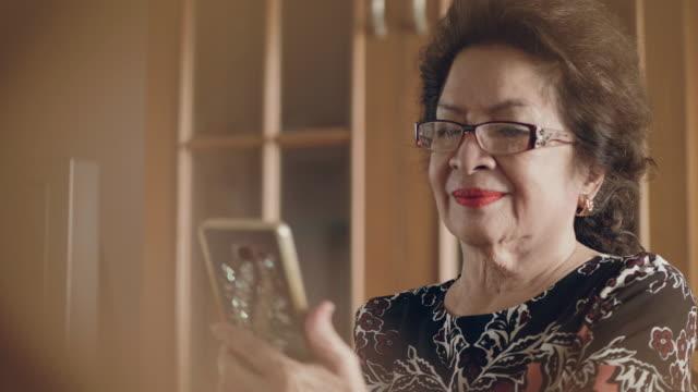 vídeos de stock, filmes e b-roll de mulher asiática sênior usar telefone inteligente na sala de estar em casa. - dispositivo de informação portátil