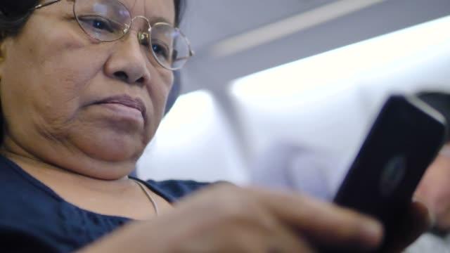 asiatisk senior kvinna använder teknik på plan. - människofinger bildbanksvideor och videomaterial från bakom kulisserna