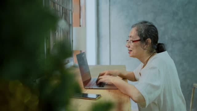 vídeos y material grabado en eventos de stock de asiática mujer mayor usando computadora portátil y mecanografía para trabajar desde casa - pueblos de asia oriental