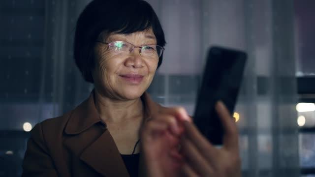 stockvideo's en b-roll-footage met aziatische hogere vrouw die mobiele telefoon bij nacht gebruikt - chinese etniciteit