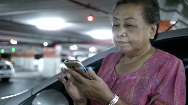 asian senior woman using smart phone at the car park - 60 69 years stock videos & royalty-free footage