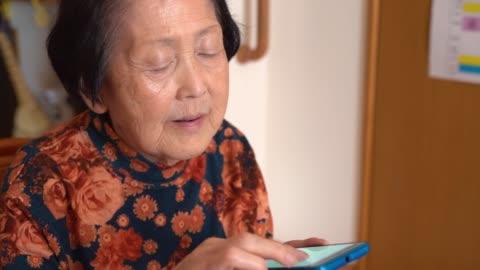 vídeos y material grabado en eventos de stock de mujer asiática senior usando teléfono inteligente - demencia
