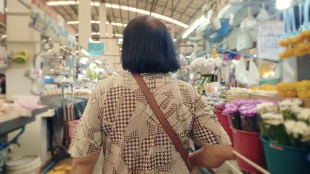 asiatische seniorin zu fuß und einkaufen in auf bauernmarkt. bangkok, thailand. - scharfe schoten stock-videos und b-roll-filmmaterial