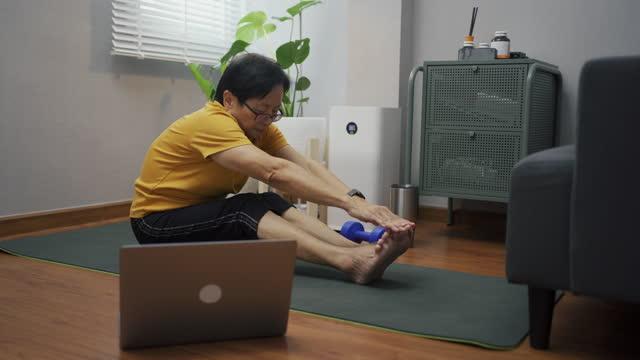 vidéos et rushes de femme âgée asiatique regardant l'entraînement vidéo et l'entraînement à la maison. - seniornaute