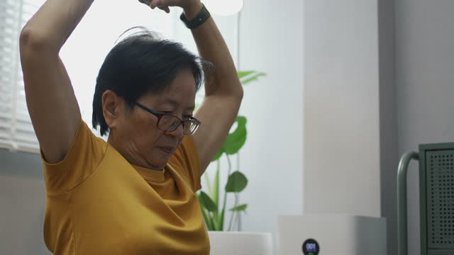 stockvideo's en b-roll-footage met asian senior woman watching video workout and training at home. - menselijke arm